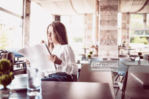 cute female reading magazine and drinking coffee - glass magazine stock photos and pictures