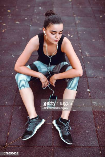 cute female relaxing from workout with music - colors soundtrack stock pictures, royalty-free photos & images