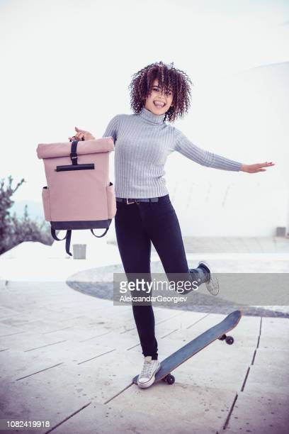 Cute Female Student Doing Skate Trick While Holding Her Backpack