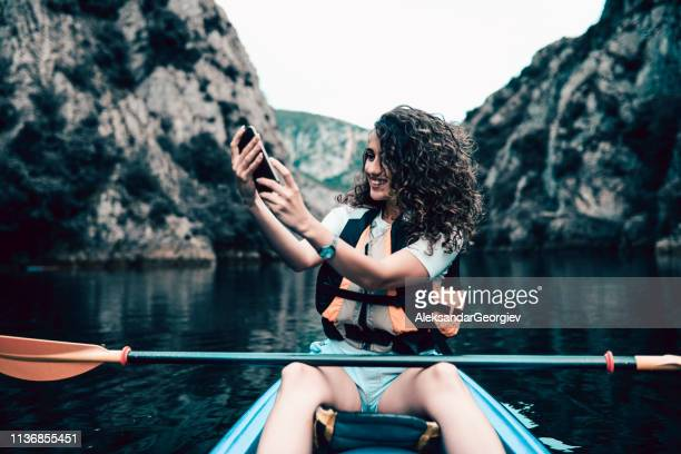 Cute Female Taking Selfie In Kayak