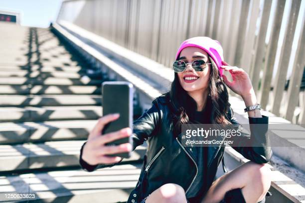 cute female taking selfie while sitting on stairs - punk music stock pictures, royalty-free photos & images