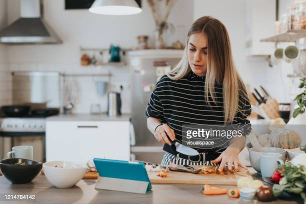 cute female teenager cooks dinner while having a video call conversation - cooking stock pictures, royalty-free photos & images