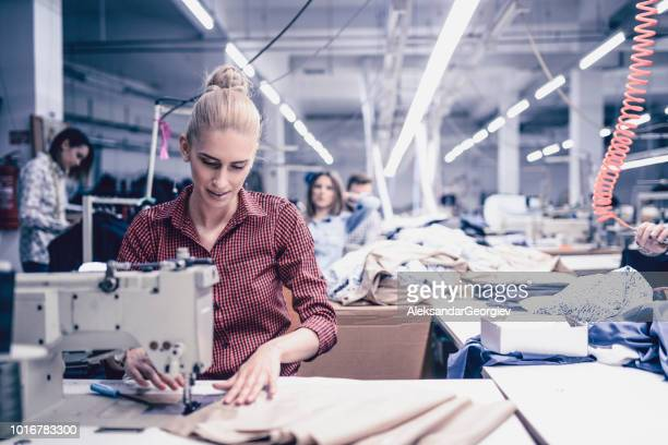 cute female textile factory worker sewing clothes on machine - embroidery stock pictures, royalty-free photos & images