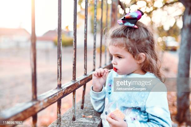 cute female toddler standing near fence outdoors and eating sweets - sugar baby imagens e fotografias de stock
