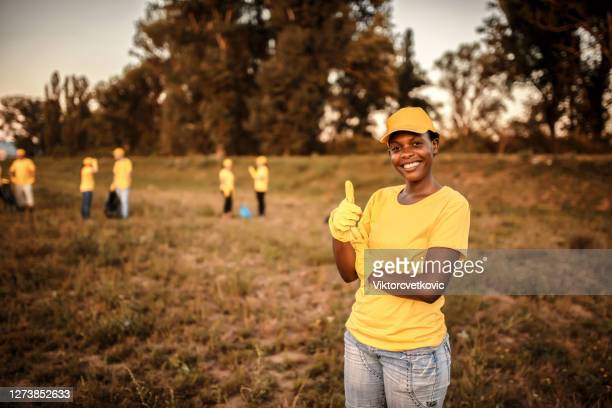 cute female volunteer cleaning garbage in nature - social justice concept stock pictures, royalty-free photos & images