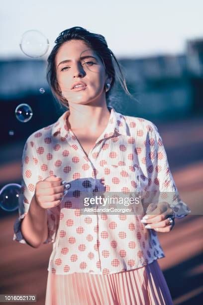 Cute Female Watching Bubbles Fly While Standing On Tennis Court