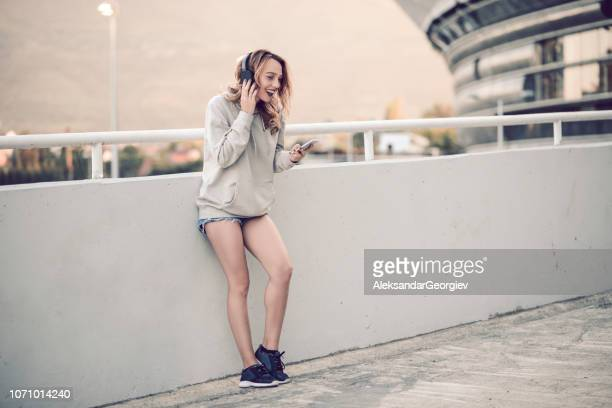 cute female watching funny videos on smartphone - hoodie headphones stock pictures, royalty-free photos & images