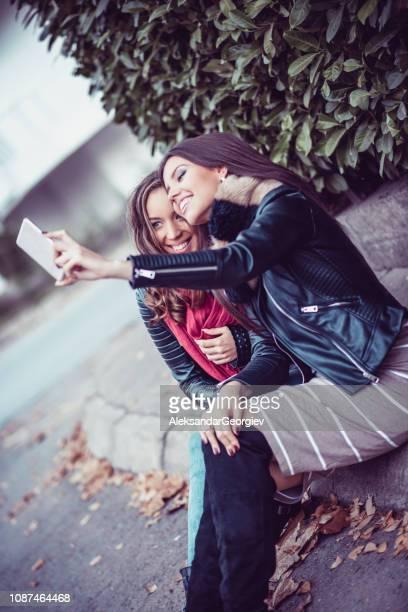 Cute Females Taking Selfie While Sitting On Sidewalk