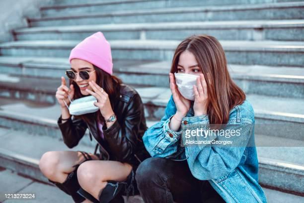 nette frauen versuchen, sich vor virus mit chirurgischen masken zu schützen - grippeschutzmaske stock-fotos und bilder