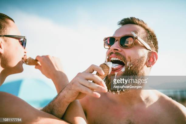 cute gay couple eating ice cream and having fun together - freaky couples imagens e fotografias de stock
