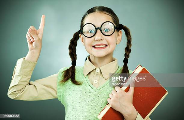 cute geek girl holding her book. - girl nerd hairstyles stock photos and pictures