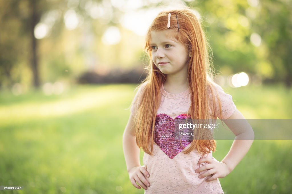 cute ginger girl posing in park stock photo | getty images