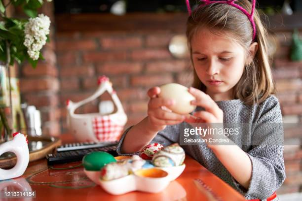 cute girl admiring colorful eggs, preparing for easter sunday, happy childhood. - easter sunday stock pictures, royalty-free photos & images