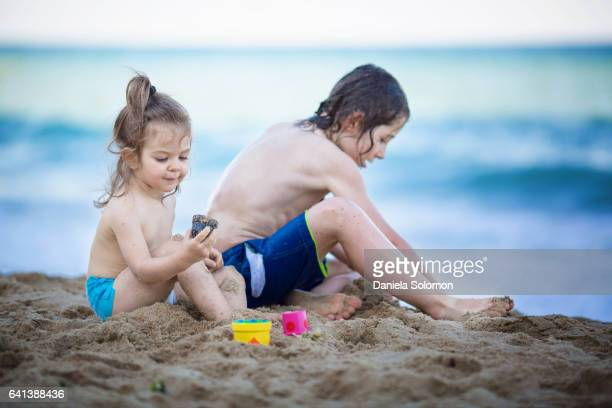 cute girl and boy enjoying sand on the beach - 2 girls 1 sandbox stock photos and pictures