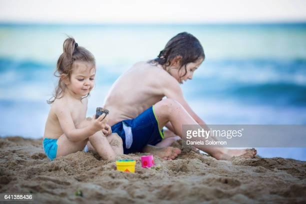 Cute girl and boy enjoying sand on the beach