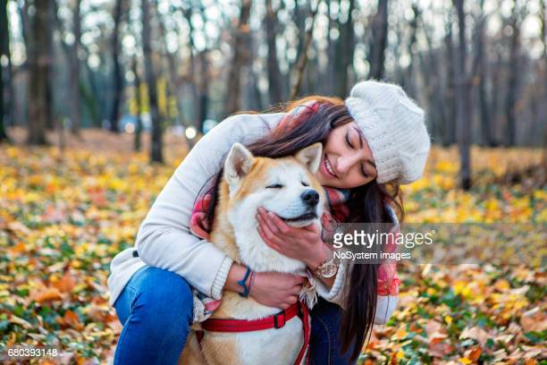 Cute girl and her dog spending day together and having fun i the public park.