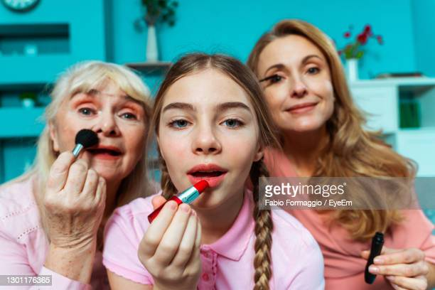 cute girl applying lipstick with parents - kids makeup stock pictures, royalty-free photos & images