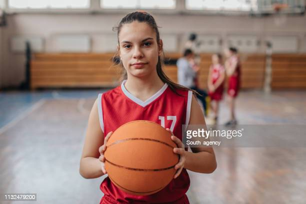 cute girl basketball player holding a basketball ball - women's basketball stock pictures, royalty-free photos & images