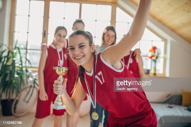jogador de basquetebol bonito da menina que prende um troféu de vencimento na frente do ônibus e dos companheiros de equipe - trophy - fotografias e filmes do acervo