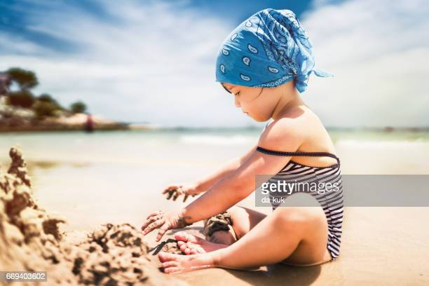 Cute girl building sand castle on tropical beach
