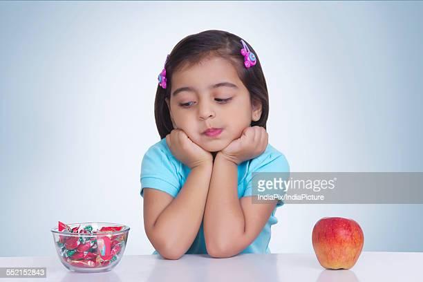 cute girl choosing between apple and sweet food against blue background - schlechte angewohnheit stock-fotos und bilder