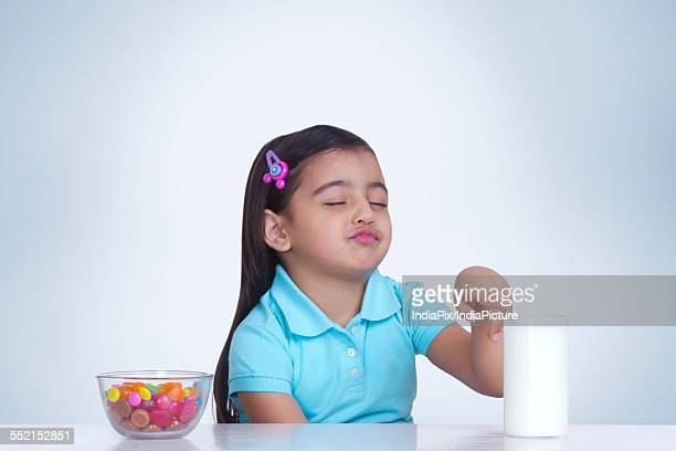 Cute girl choosing between milk and bowl of sweet food against blue background