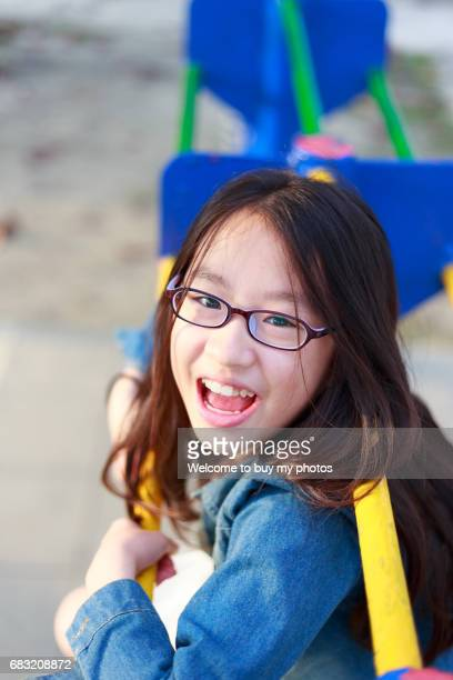 cute girl climbing and hanging on the school playground. - lying in state stock pictures, royalty-free photos & images