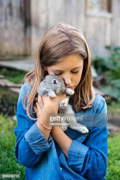 Linda chica abrazando un conejo bebé sobre su cabeza al aire libre en primavera.