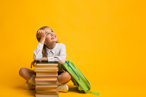 Cute Girl Dreaming About School Sitting With Backpack And Books 1169134968