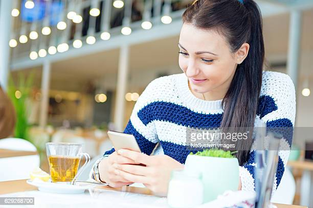 Cute girl, drinking tea in caffe, texting on cell phone