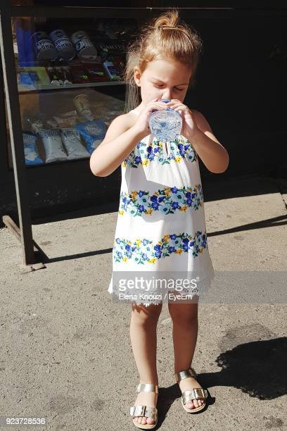 cute girl drinking water from bottle on footpath - elena knouzi stock pictures, royalty-free photos & images