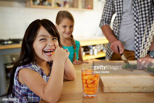 Cute girl eating baby carrots in kitchen