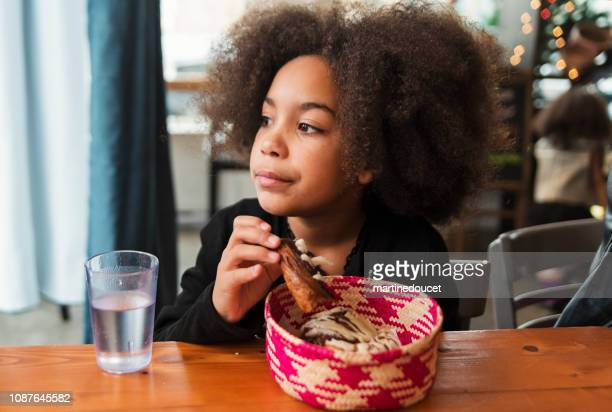 Cute girl eating cinnamon bun in restaurant in winter.