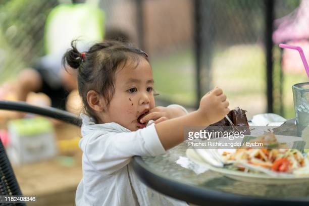 cute girl eating food in plate on table - phichet ritthiruangdet stock photos and pictures