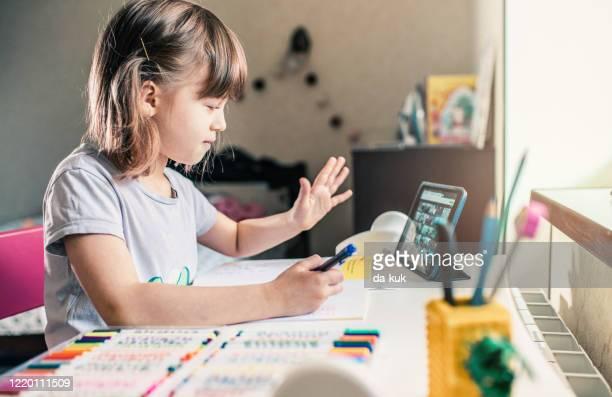 cute girl e-learning at home. - distante foto e immagini stock