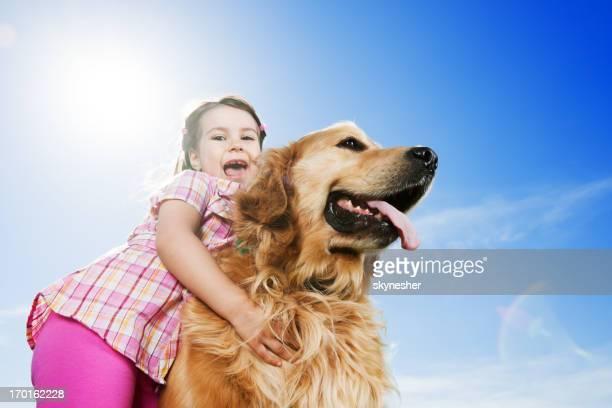 Süßes Mädchen umarmen Ihr Hund gegen den Himmel.