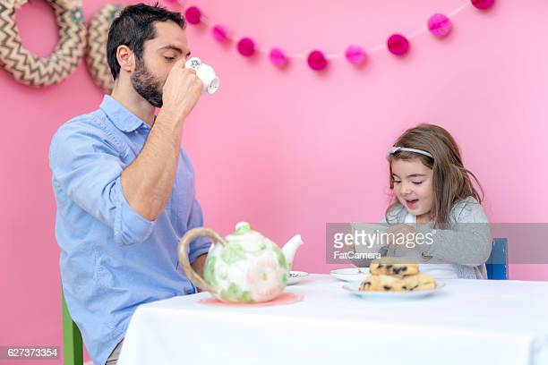 Cute girl enjoying a tea party with her ethnic father