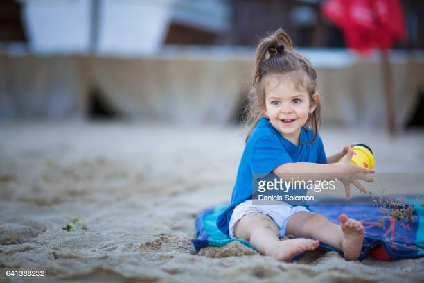 Cute girl enjoying sand on the beach