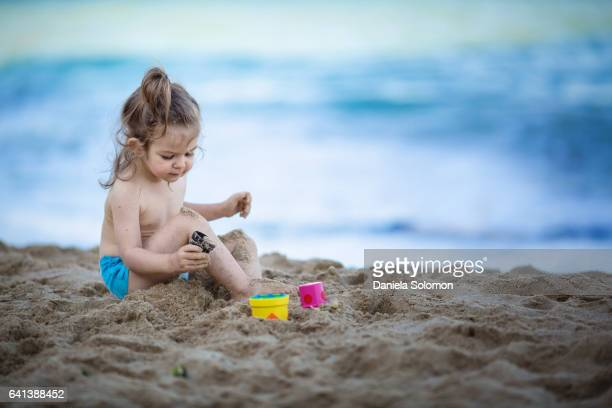 cute girl enjoying sand on the beach - 2 girls 1 sandbox stock photos and pictures