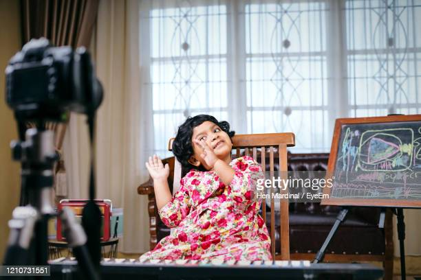 cute girl gesturing while sitting by piano at home - heri mardinal stock pictures, royalty-free photos & images