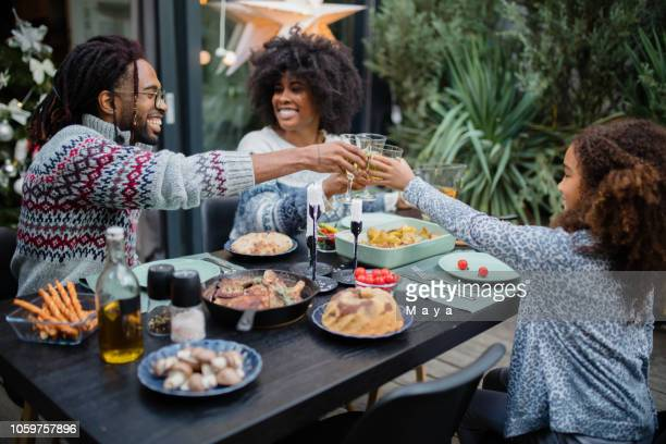 linda chica cenando con los padres - african american family dinner fotografías e imágenes de stock