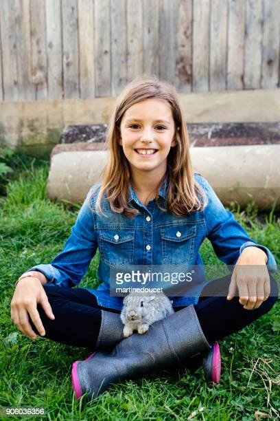 Linda chica con un conejo bebé al aire libre en primavera.