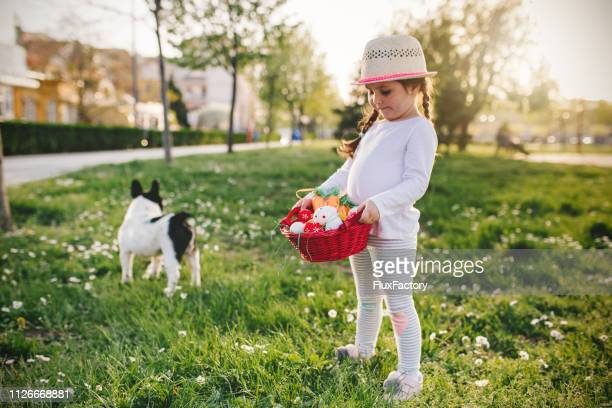 cute girl holding a basket full of easter eggs in the park - dog easter stock pictures, royalty-free photos & images