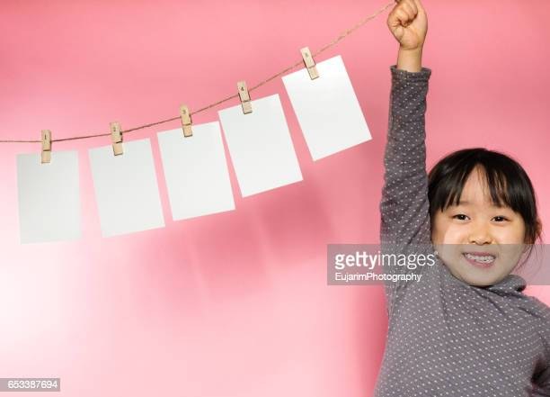 Cute girl holding a clothesline with five sheets of white paper