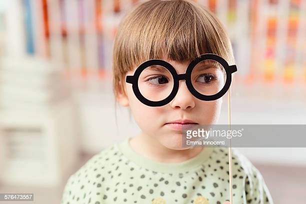 cute girl holding black paper spectacles