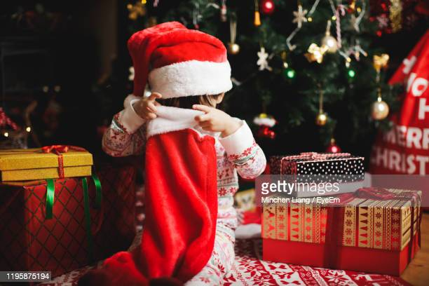 cute girl holding christmas stocking - stockings photos stock pictures, royalty-free photos & images
