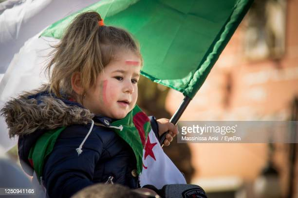 cute girl holding flag in city - algeria stock pictures, royalty-free photos & images