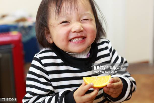 cute girl holding lemon slice at home - grimacing stock pictures, royalty-free photos & images