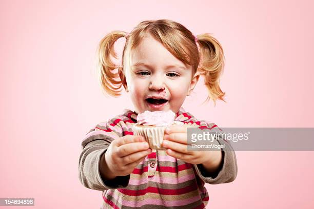 Linda chica sosteniendo rosa magdalena con glaseado