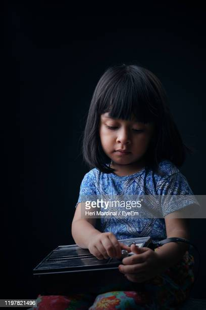 cute girl holding radio against black background - heri mardinal stock pictures, royalty-free photos & images